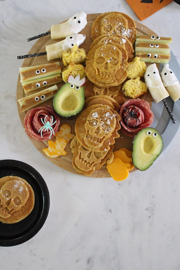 Halloween themed snack board with skeleton waffles, fruit and vegetables